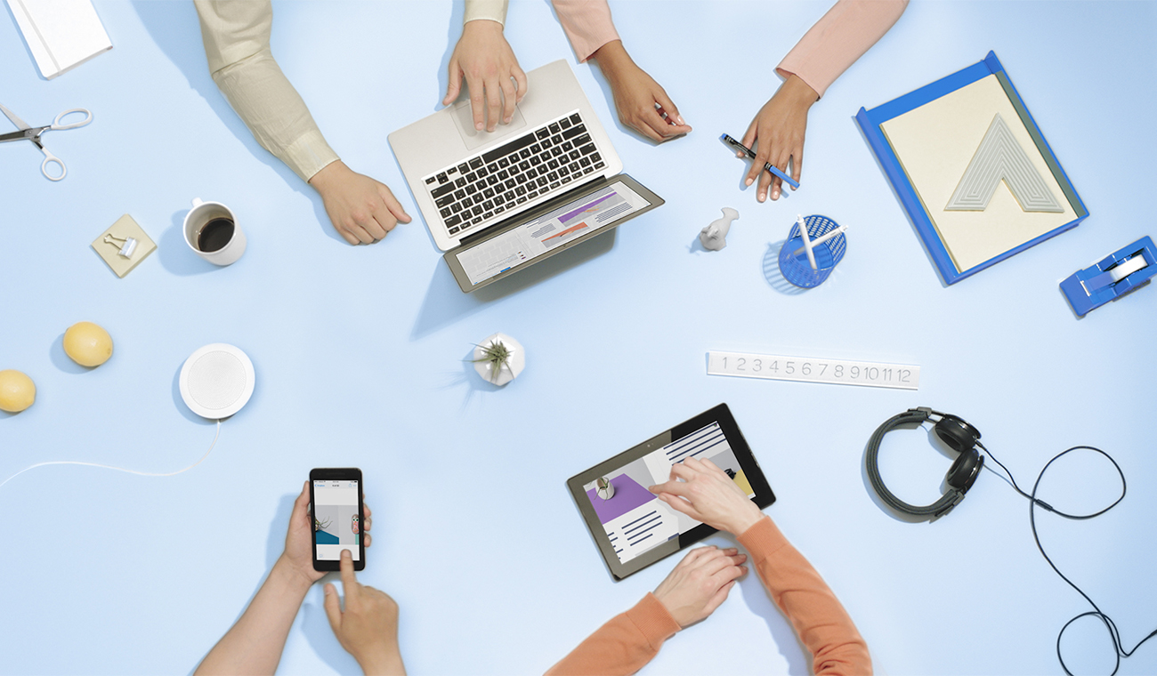 Overhead view of several people working on computers, tablets, and phones with their hands.