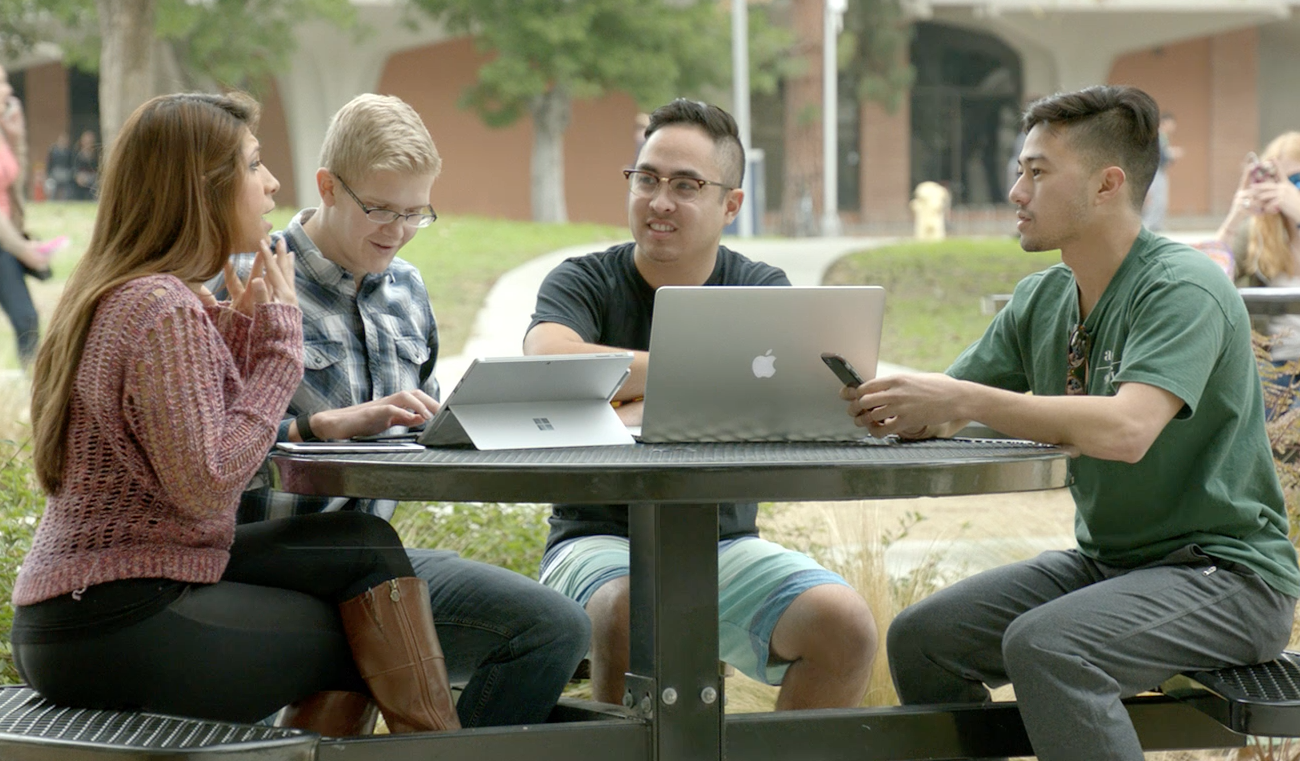 Four college students sitting around a picnic table outside, talking over laptops and tablets.