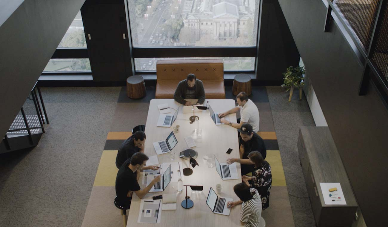An image of a group of people sitting around a conference table working on laptops.