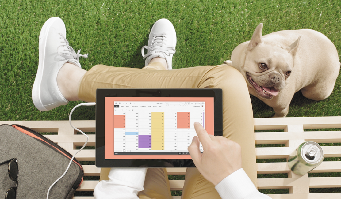 A person sitting on a park bench, using a calendar app on a tablet, with a dog sitting nearby on the grass.