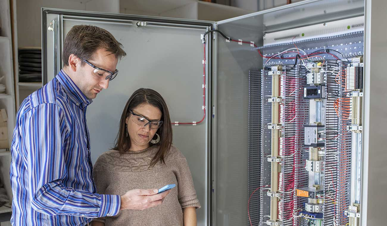 Photo of two CEL Electric employees looking at a smartphone