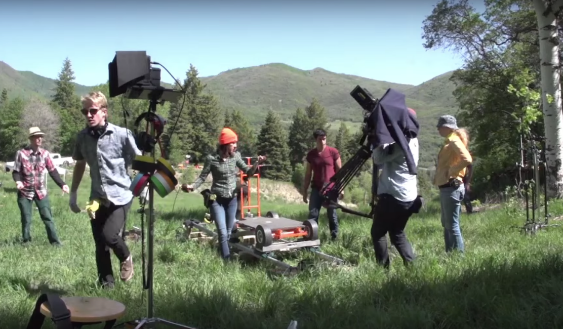 A film crew packs up equipment in an outdoor location