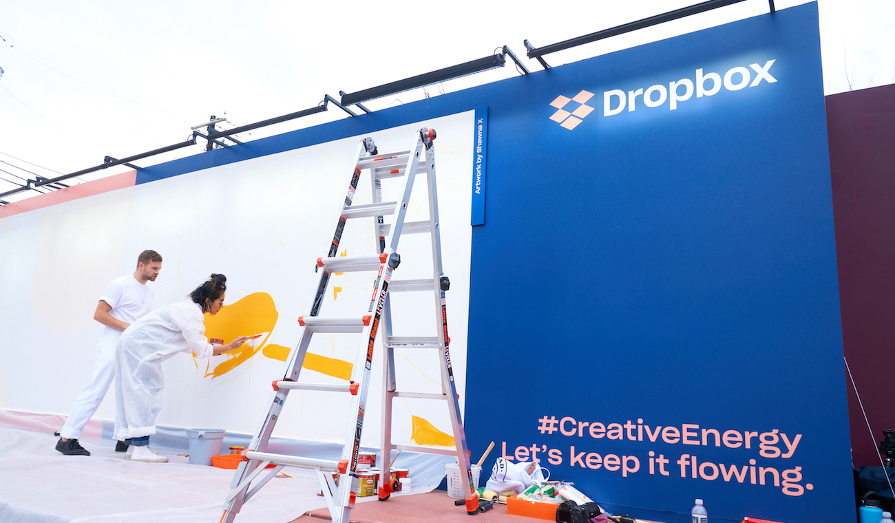 Photo of artists working on a Dropbox mural at SXSW 2018