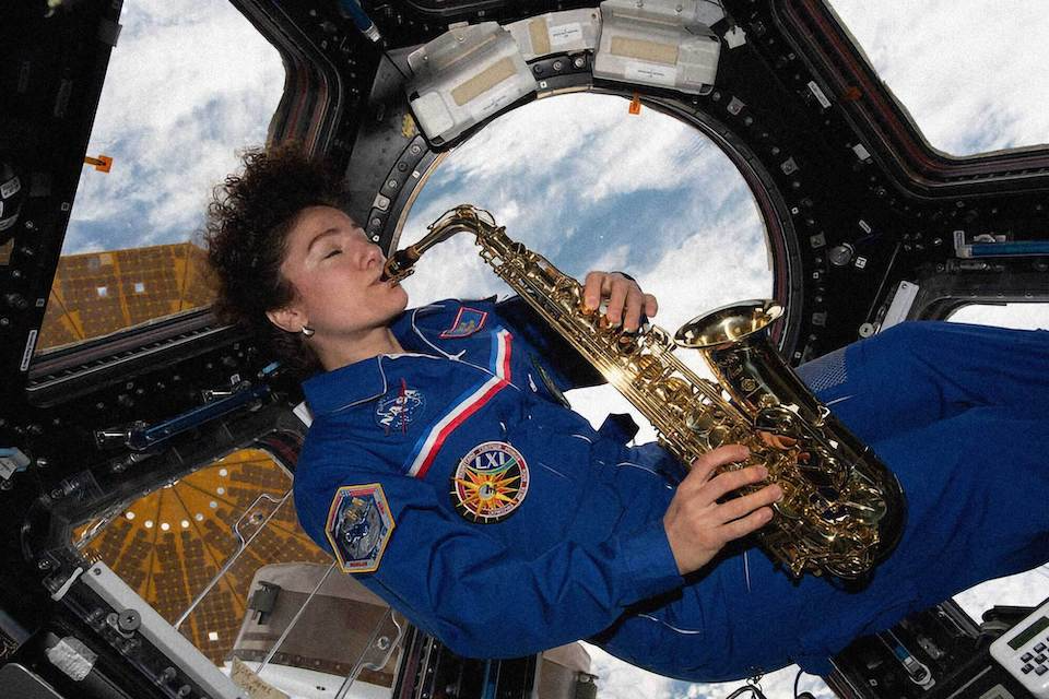 Photo of astronaut Jessica U. Meir playing sax in the Cupola. (credit: NASA)