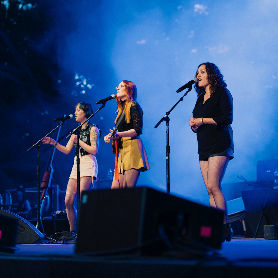 Photo by Grace Brown of Bess Rogers and Allie Moss on stage with Ingrid Michaelson