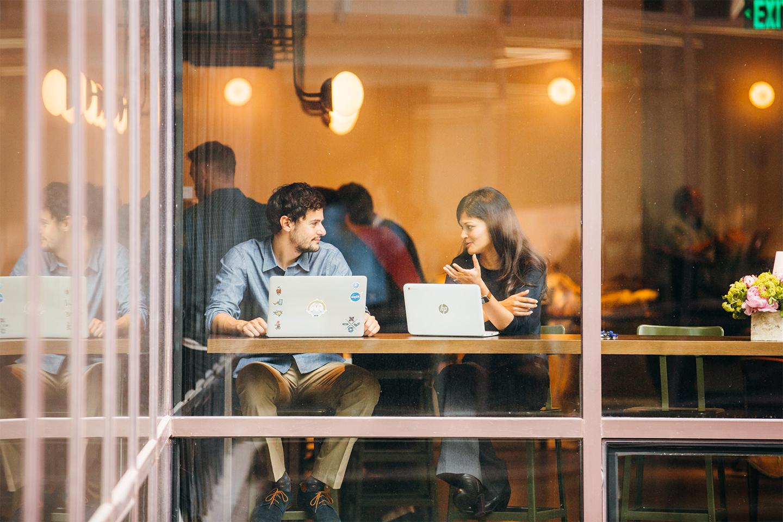 カフェで仕事をしながら話をする 2 人の人物