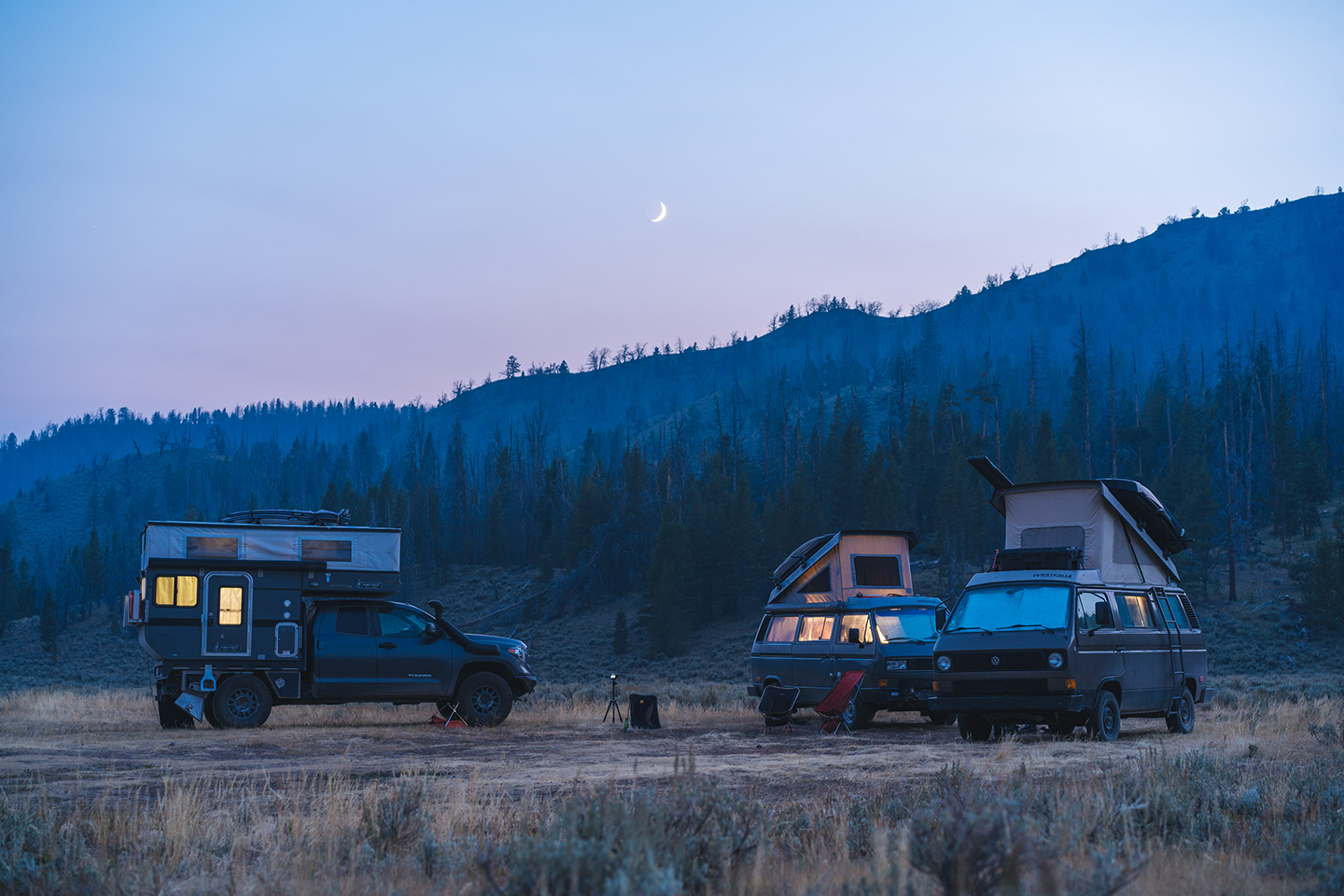 Three camper vans are parked in an open field at dusk.