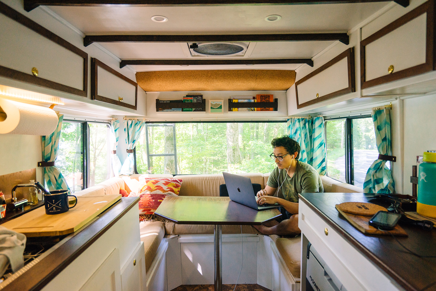 A man sits inside a camper van and works on his laptop.