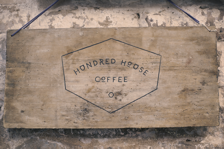 Logo Hundred House Coffee sur une planche en bois