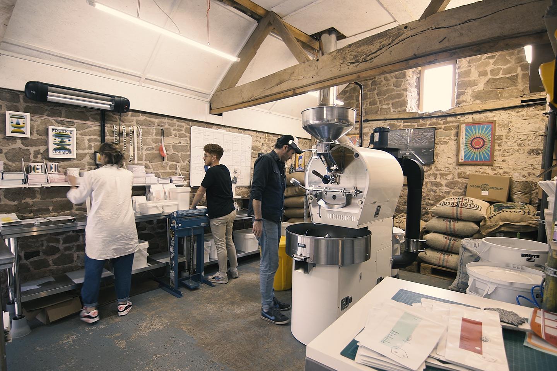 Deux hommes et une femme travaillent dans l'arrière-salle d'un atelier de torréfaction