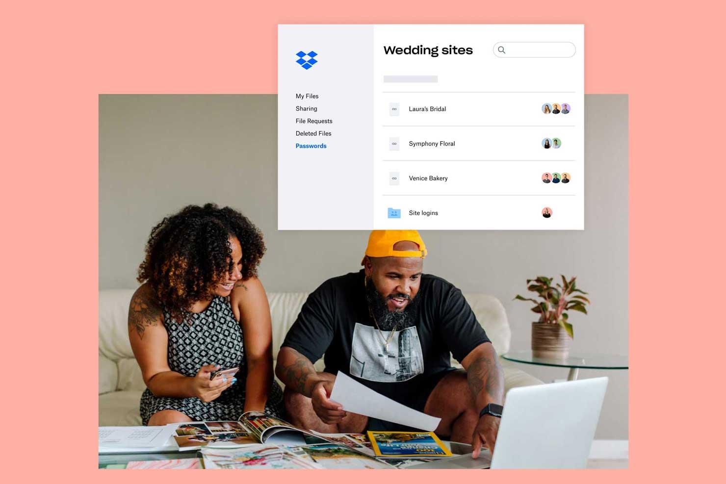 Couple assis sur un canapé avec une pile de papiers et un ordinateur portable sur une table basse, regardant un dossier de mariage dans Dropbox