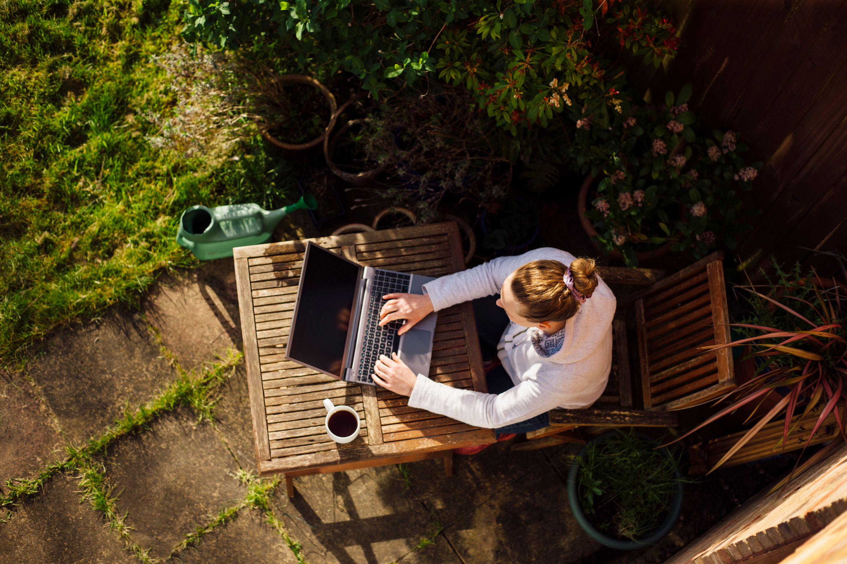 A person remotely working outdoors on a laptop