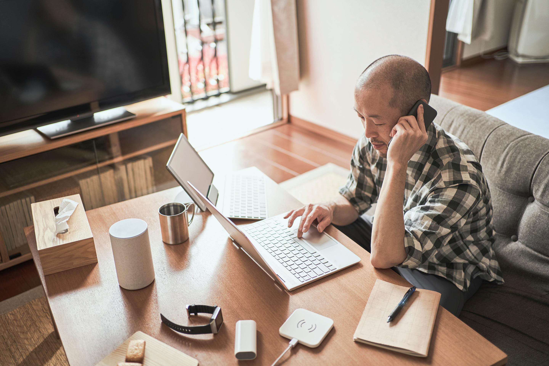 Personne qui discute du travail à distance au téléphone tout en travaillant sur un ordinateur portable