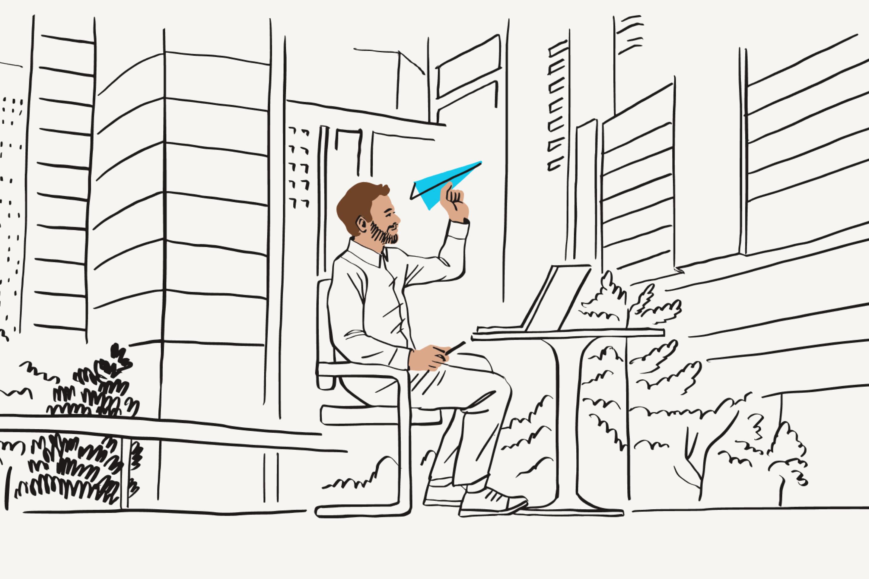 Un hombre teletrabajando fuera de casa mientras lanza un avión de papel