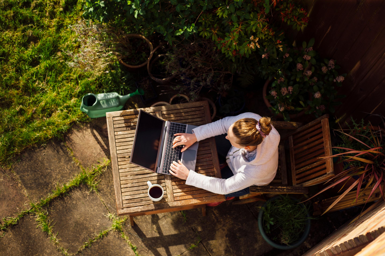 Una persona trabajando a distancia al aire libre en una computadora portátil