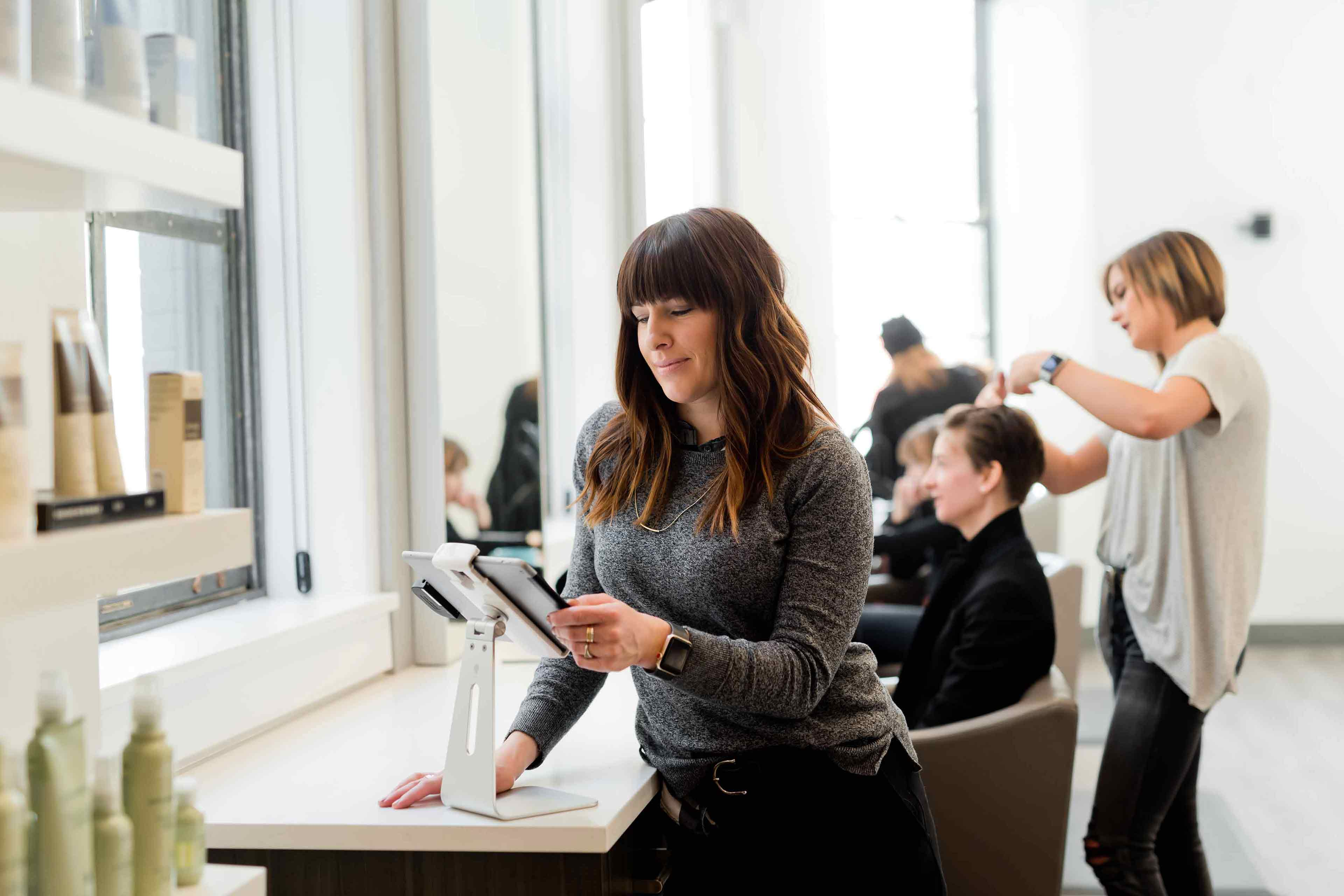 Someone in a hair salon uses a touchscreen mobile device to grow their small business