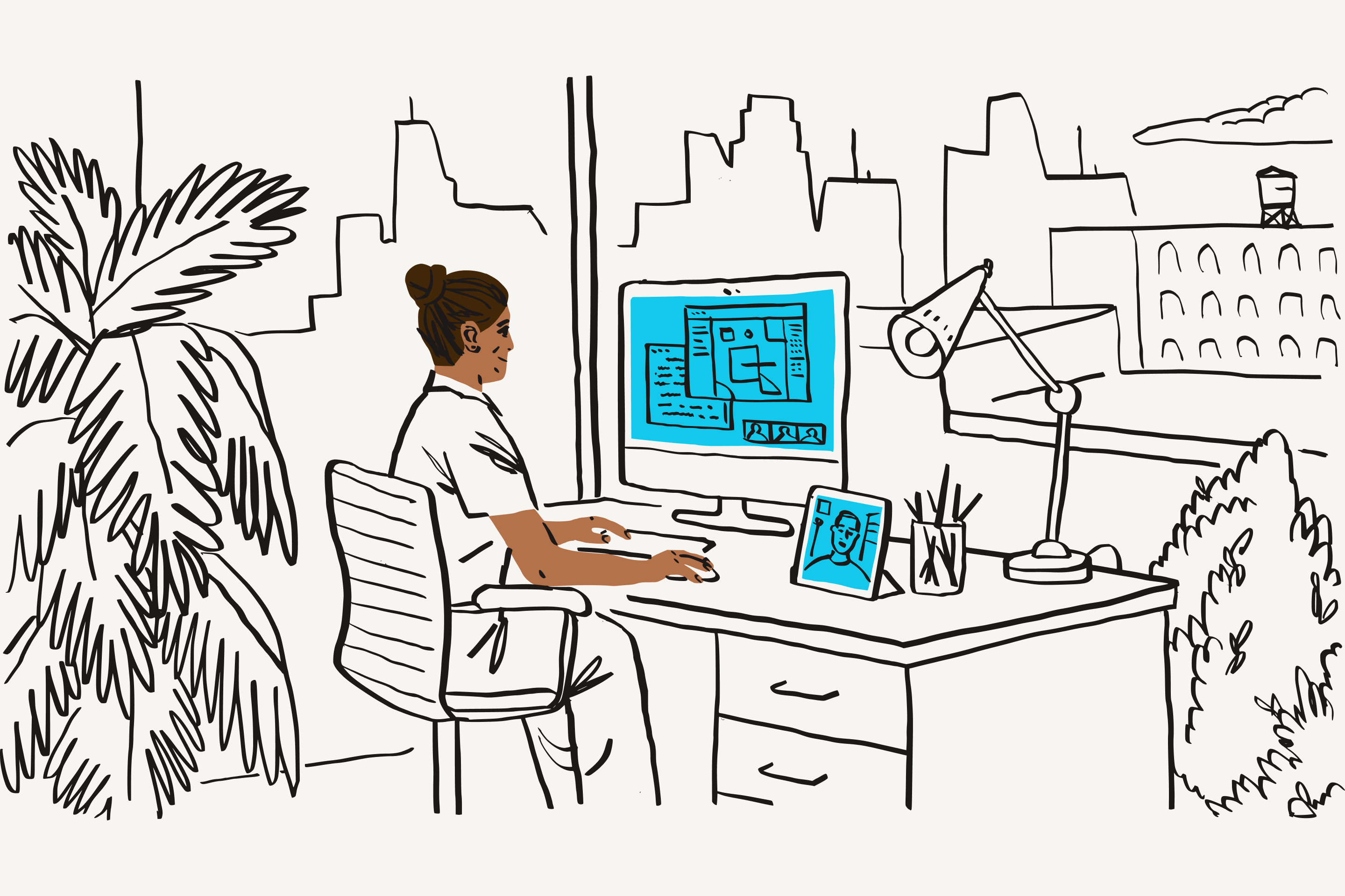 A woman works on a computer while sitting at her desk