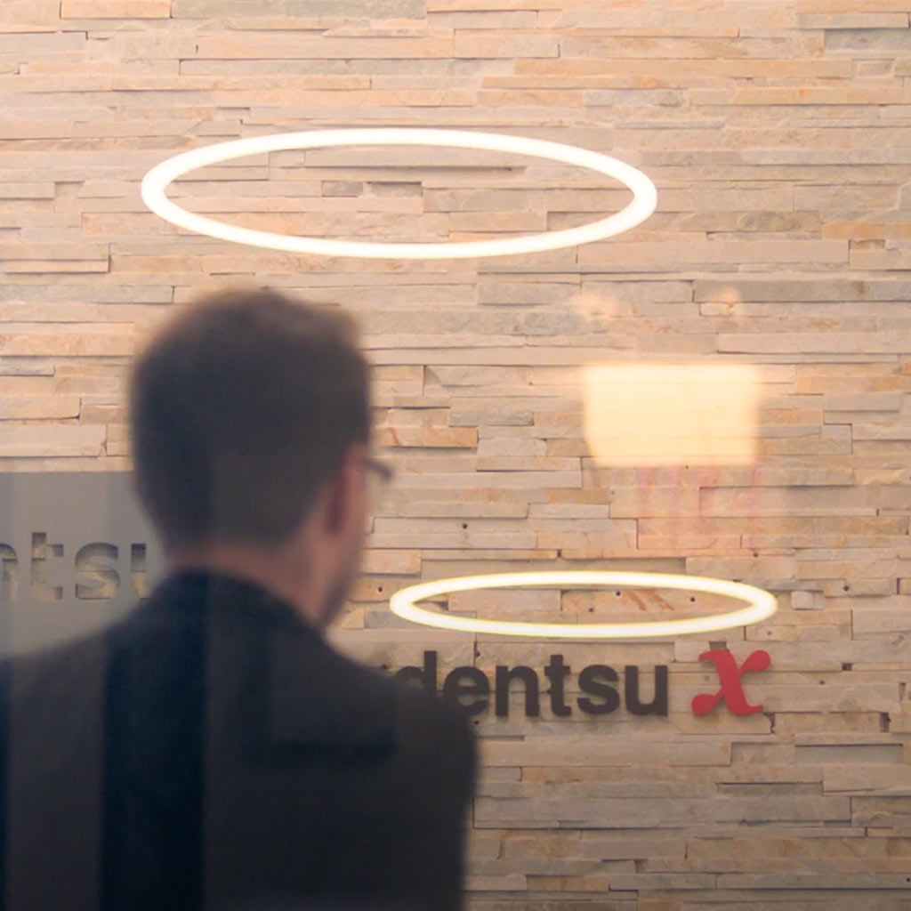 A man in front of the Dentsu logo