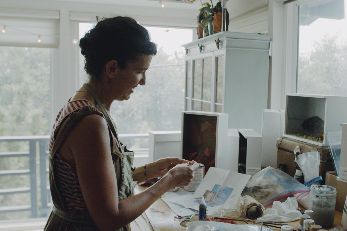 Kobieta przy stanowisku pracy pracująca nad małym modelem