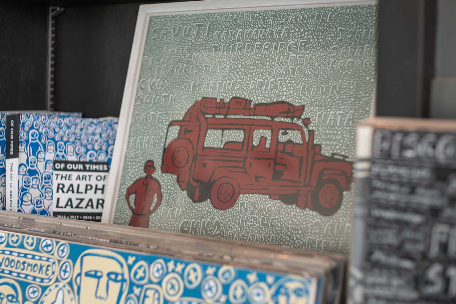 Photo of framed illustrations of a red safari truck and a blue abstract face