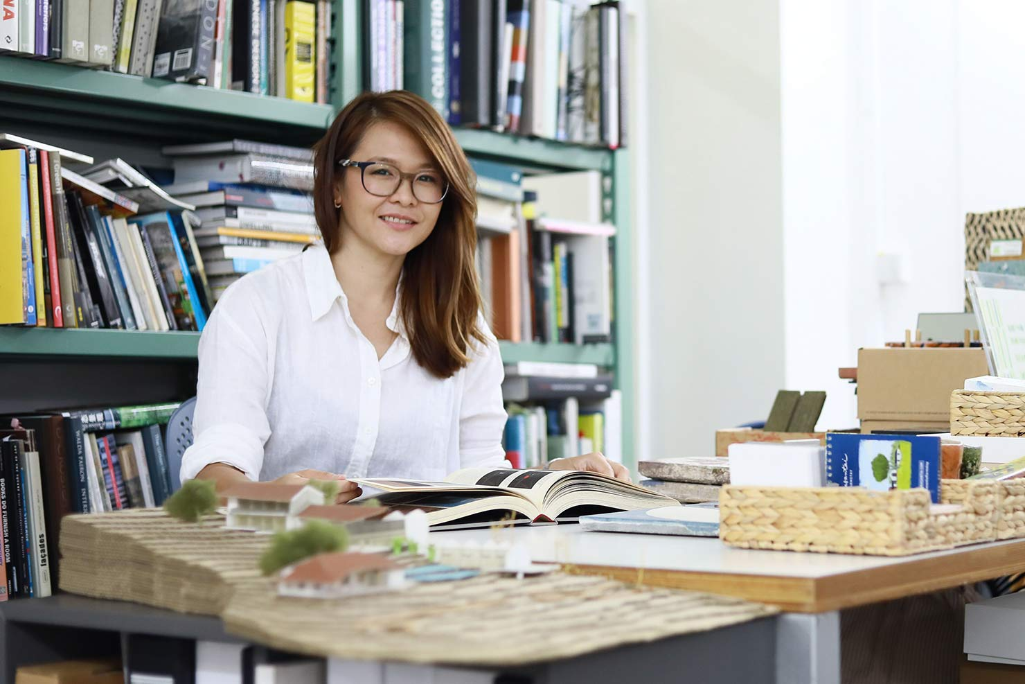 Woman in white shirt and glasses reading from a book in a workspace