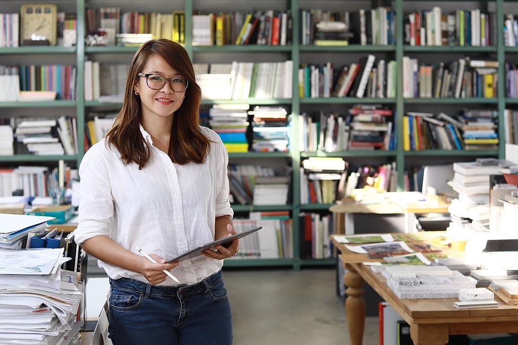 Seorang wanita sedang bekerja menggunakan tablet di depan rak yang berisi buku dan map