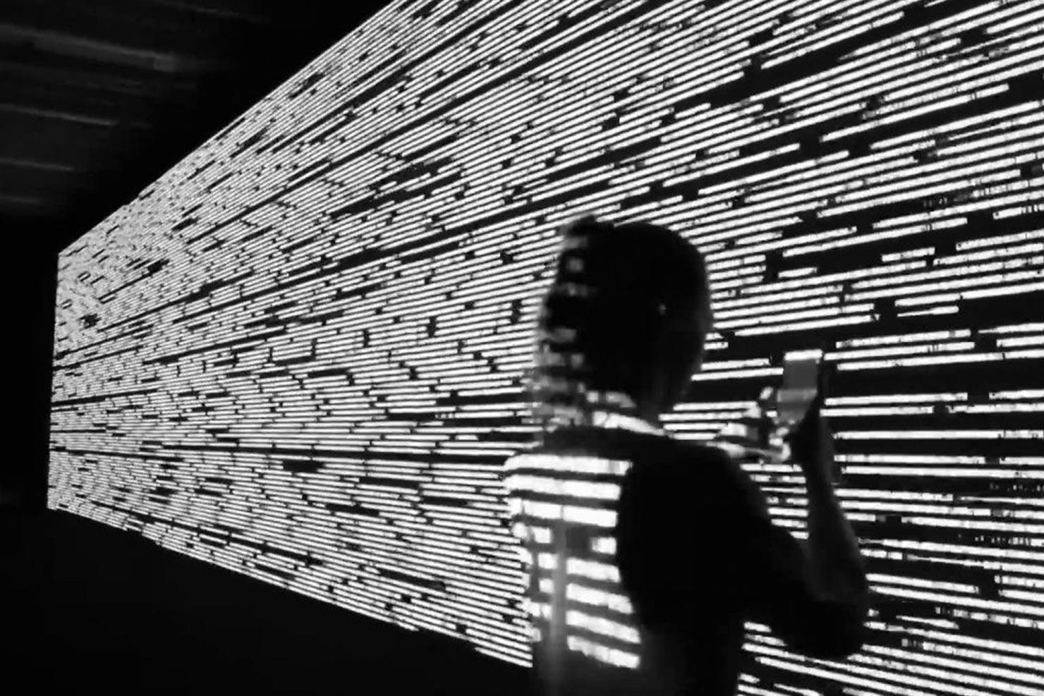 Svart/hvitt-bilde av statiske skygger som dekker en person som ser på telefonen