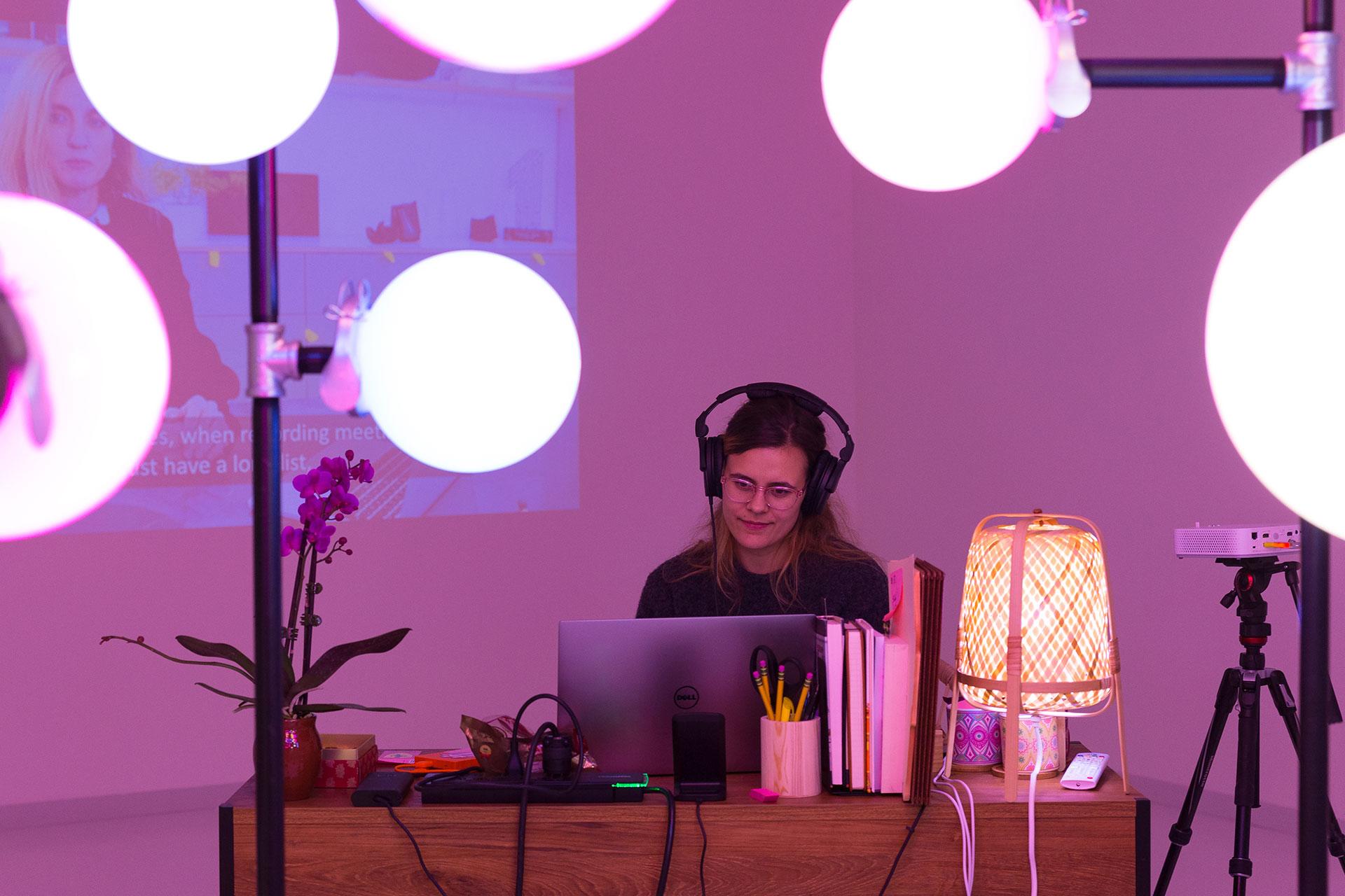 Kvinne med hodetelefoner, ser på en datamaskin bak rosa lys på stativer