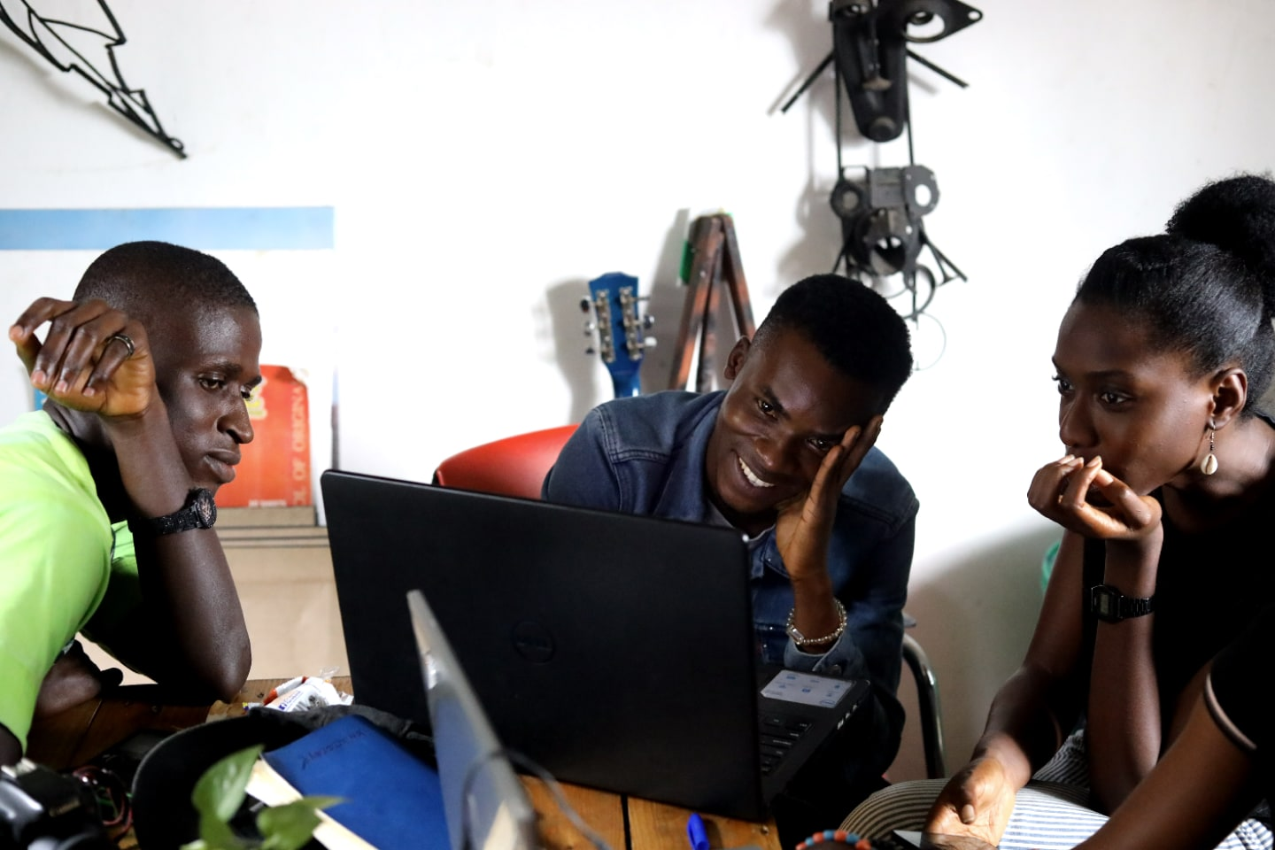 Three people look at a computer screen.