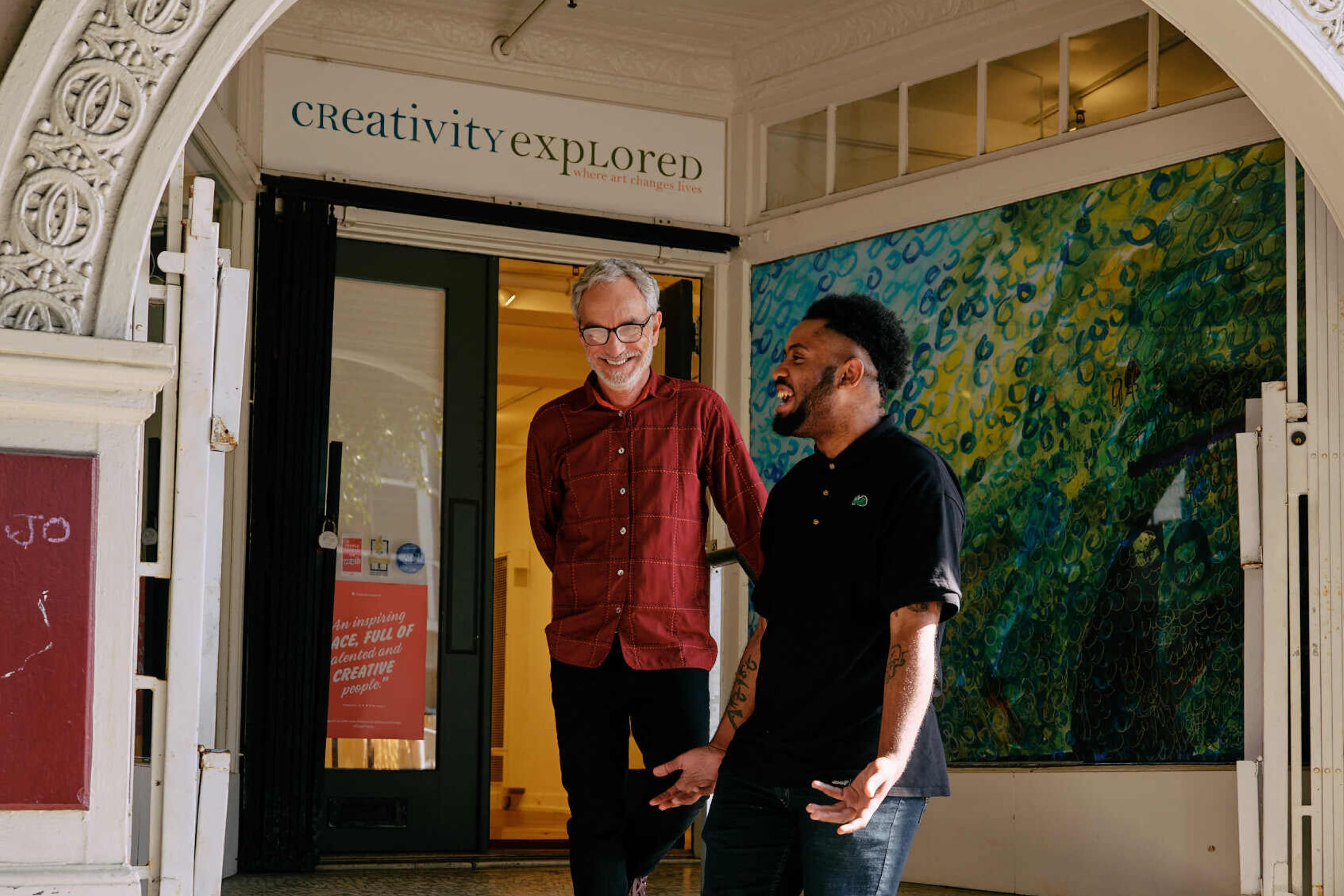 """Joseph """"JD"""" Green and Glenn Peckman laugh together outside of Creativity Explored."""