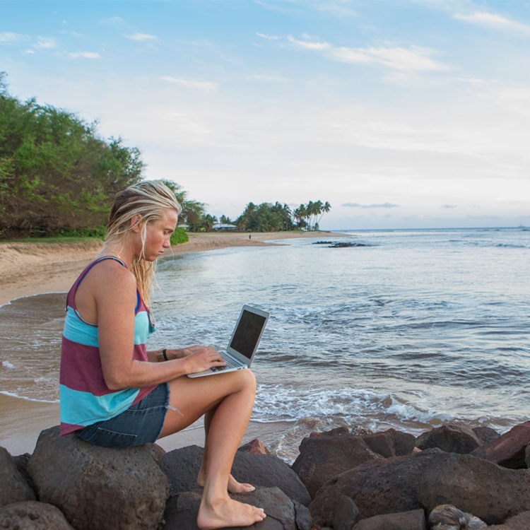Woman using laptop next to the ocean