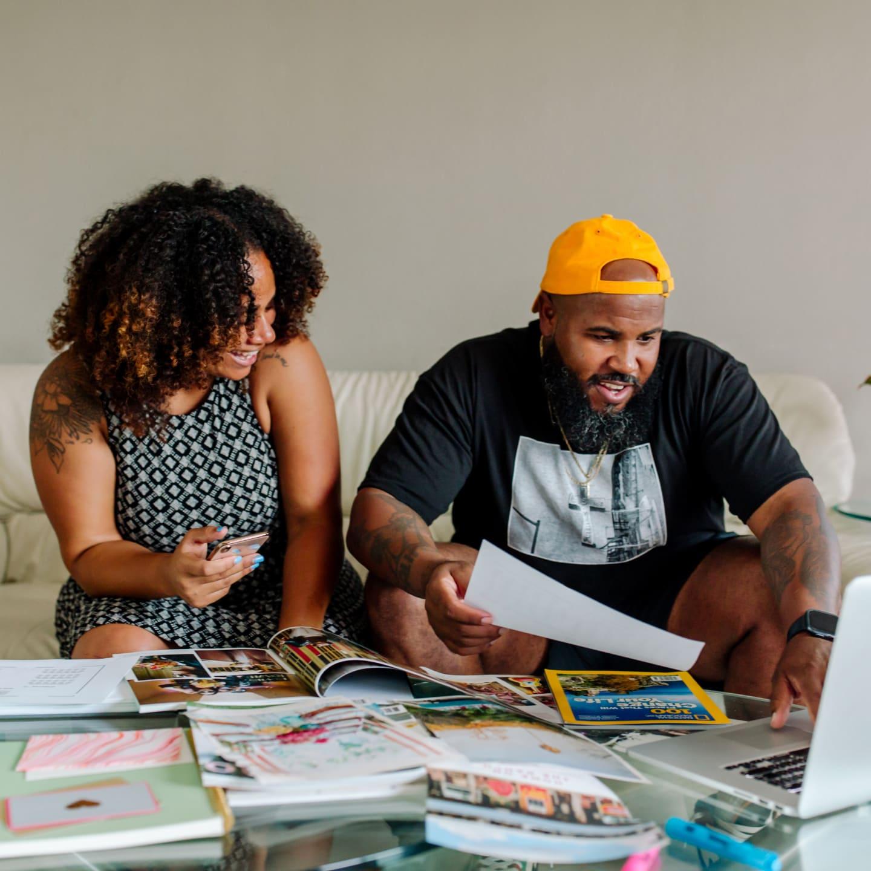 Twee mensen kijken naar een laptop terwijl ze door tijdschriften bladeren.