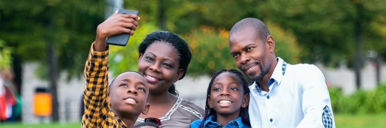 Een gezin poseert samen voor een foto met een mobiel apparaat.