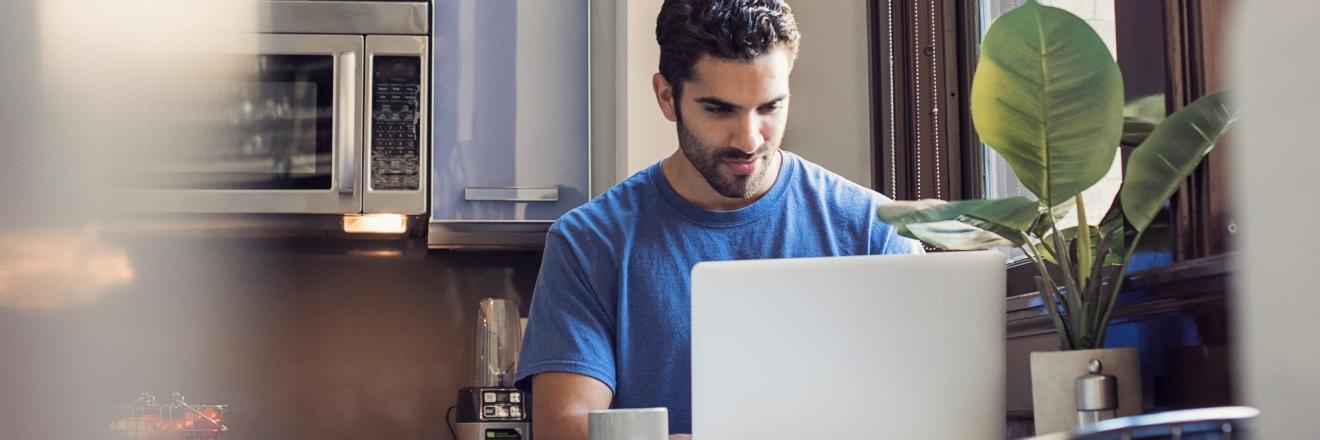 Een man werkt aan de keukentafel op zijn laptop.
