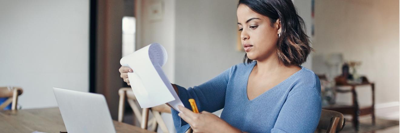 Een vrouw bladert aan haar bureau door papieren.