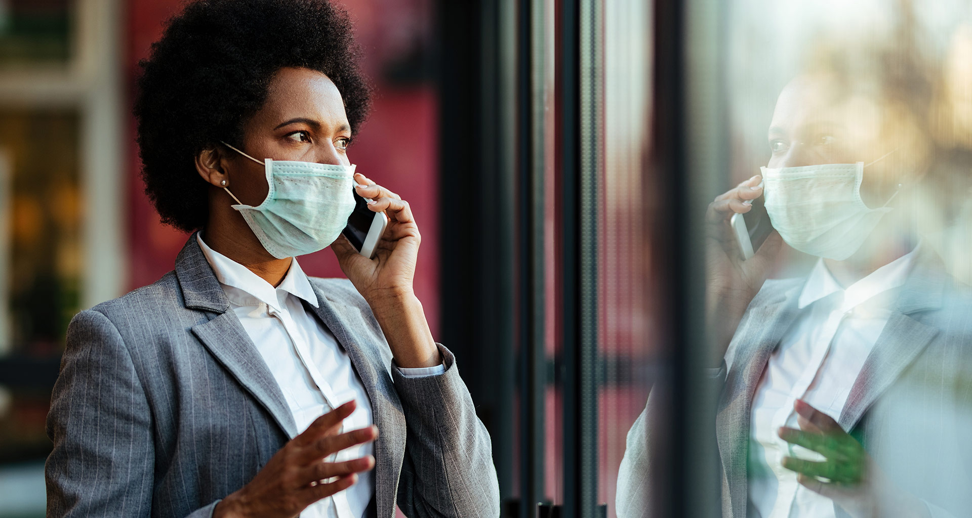 A person in a business suit is wearing a mask and talking to a person over the phone