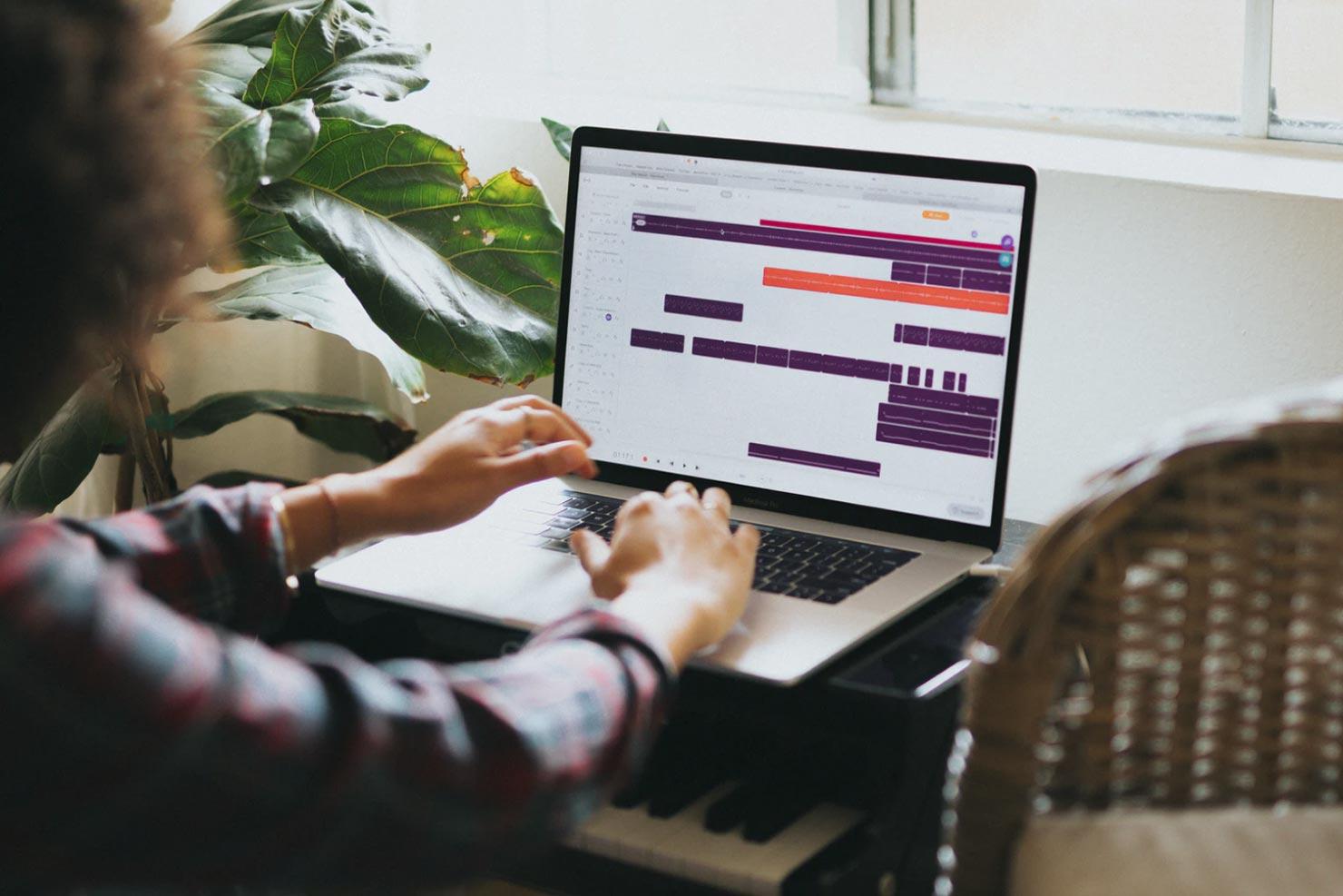 Pessoa trabalhando em um laptop aberto com uma ferramenta de agendamento na tela