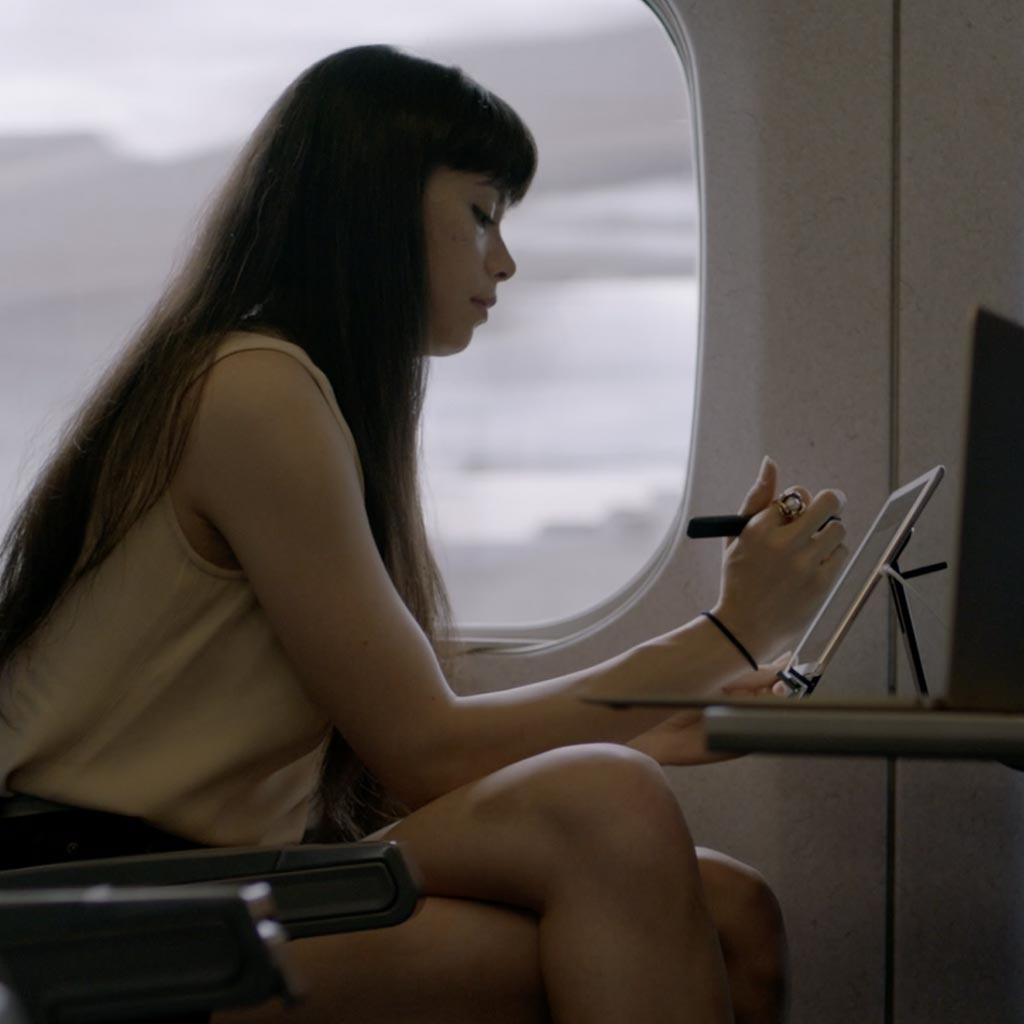 A person working on a tablet from a plane shows how work is becoming flexible