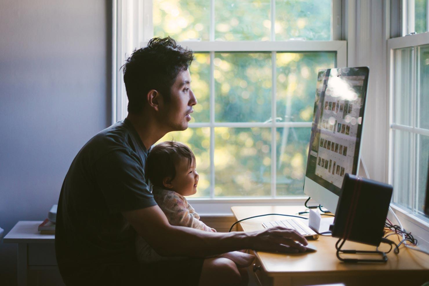 Jovem pai com bebê no colo trabalhando em um monitor de computador