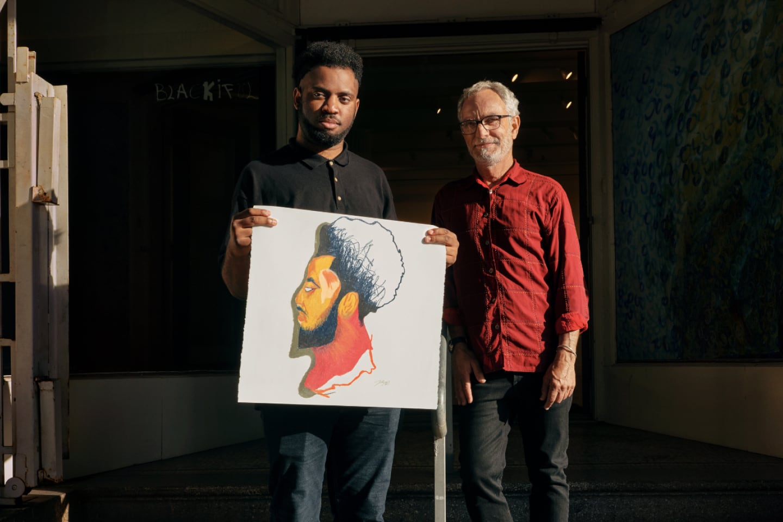 "Joseph ""JD"" Green and Glenn Peckman of Creativity Explored hold up a piece of art."
