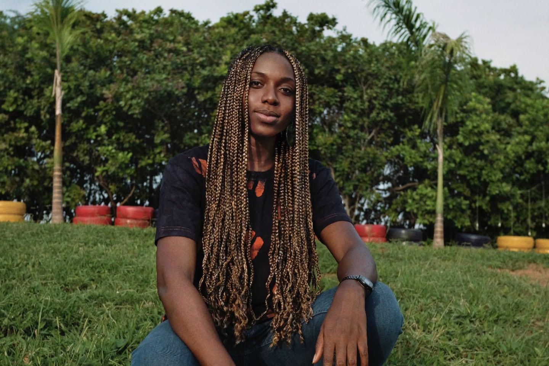 Benita Nnachortam, a Nigerian photographer, entrepreneur, and activist, sits in a field.