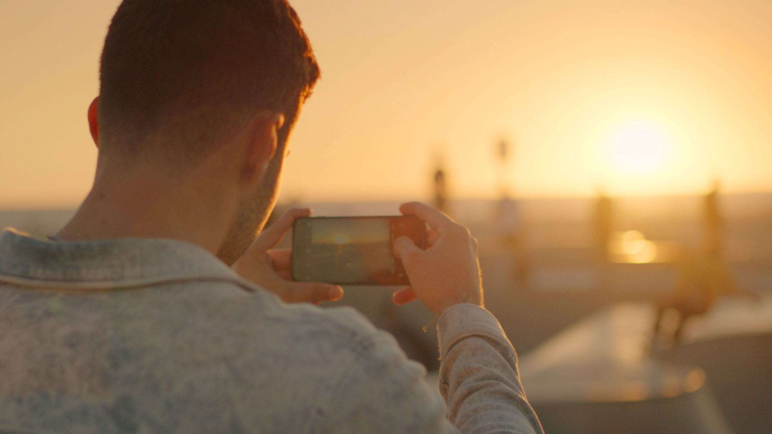A person taking a photo of a sunset using their mobile phone
