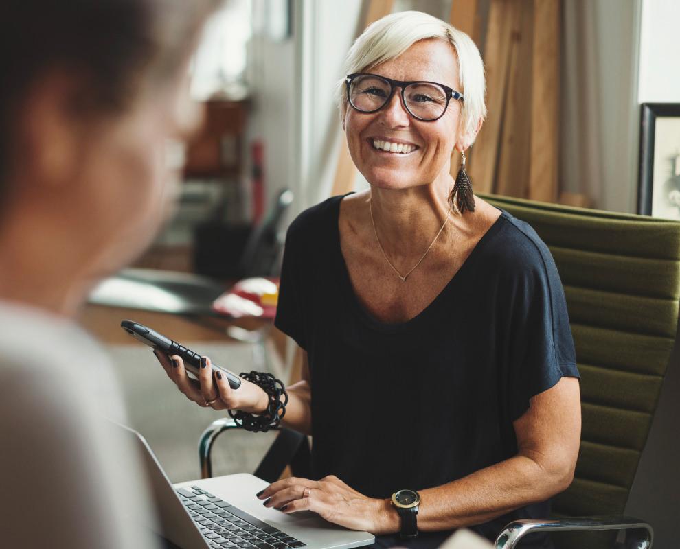 Een lachende vrouw werkt op een mobiele telefoon en computer