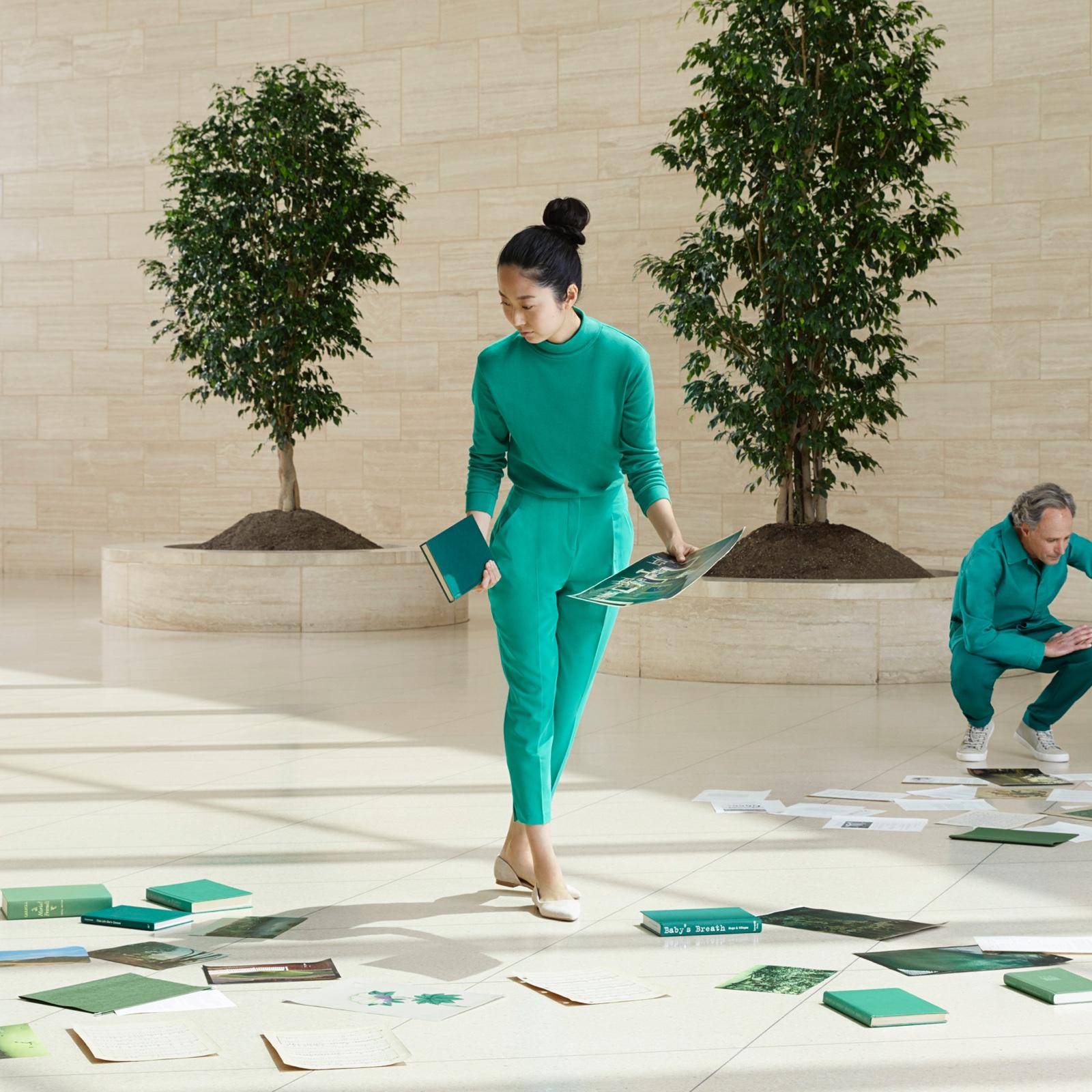ผู้หญิงในชุดสีน้ำเงินอมเขียวยืนถือหนังสือและกระดาษ ล้อมรอบไปด้วยหนังสือที่วางอยู่บนพื้น ผู้ชายและผู้หญิงในชุดสีน้ำเงินอมเขียวหมอบอยู่บนพื้นที่ล้อมรอบไปด้วยกระดาษและหนังสือ กำลังมองไปที่หนังสือ