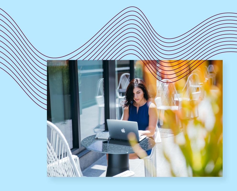 Kobieta pracująca na laptopie przy stoliku na świeżym powietrzu