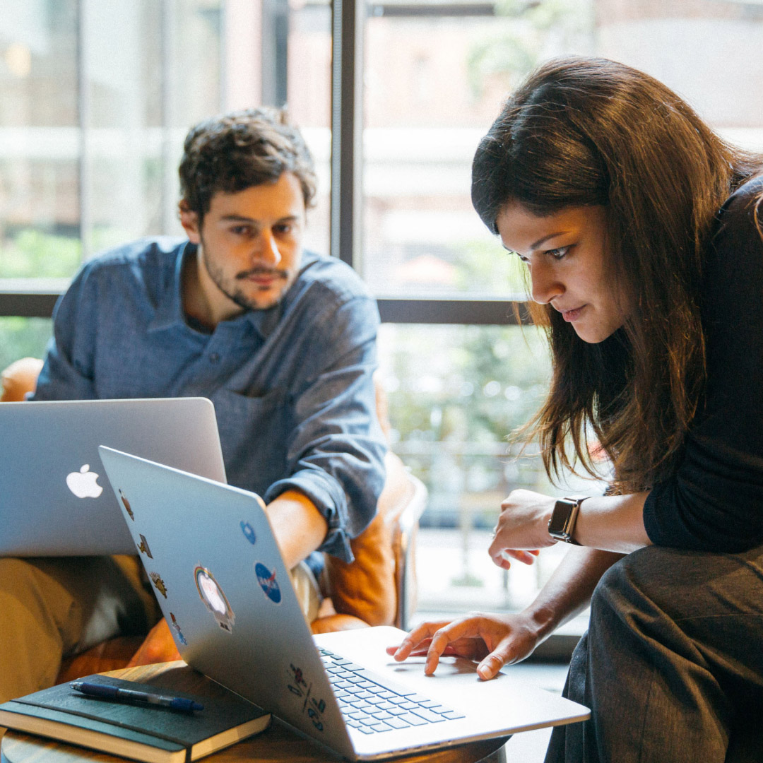 Una mujer está trabajando en su portátil cuando un hombre se inclina hacia el borde de su pantalla para mirar el contenido.