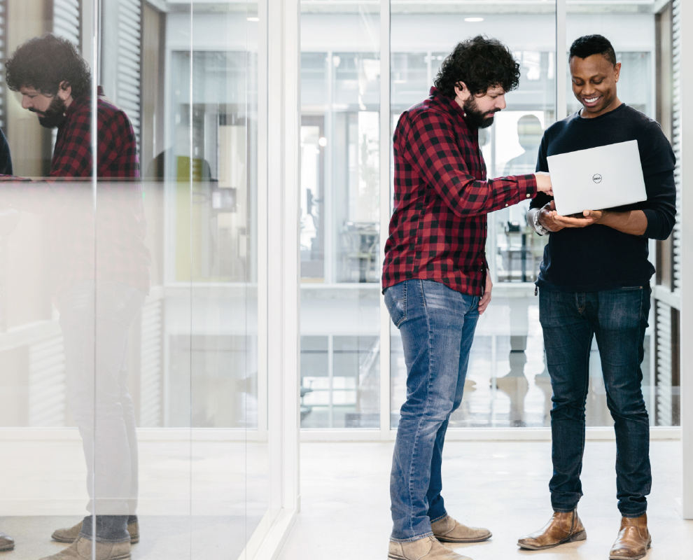 Two team members stand in an office talking while looking at IDG research on how you can get the most out of collaboration