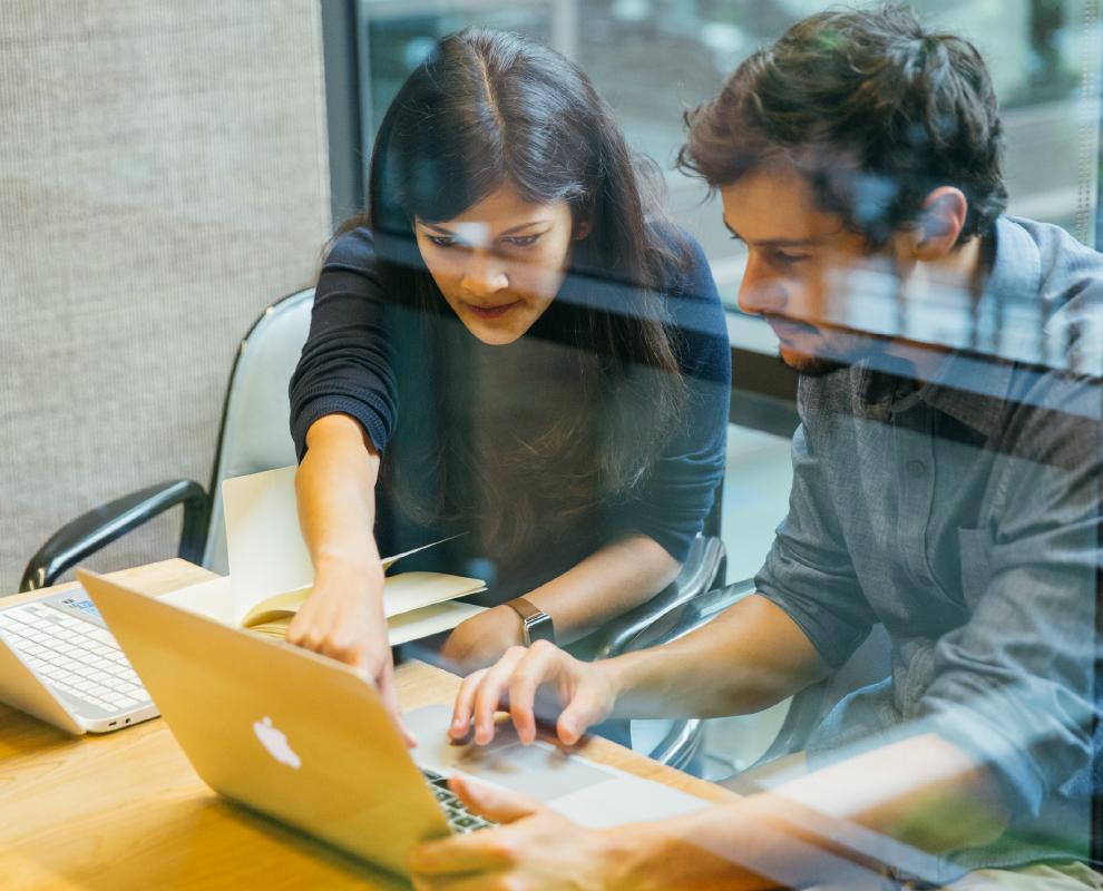 Compañeros de trabajo que comparten un escritorio y un portátil, mientras comentan el estado de la colaboración en su lugar de trabajo