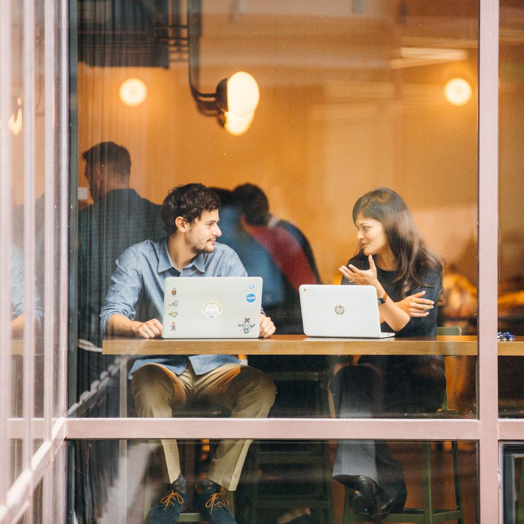 Два человека сидят у окна и разговаривают друг с другом, отведя взгляд от экранов своих ноутбуков.