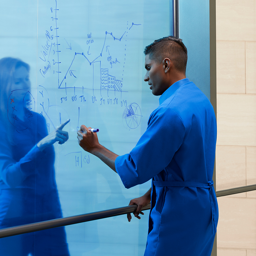 A man draws a graph on a transparent whiteboard while a woman points at board.